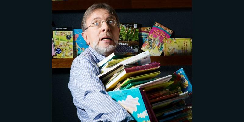 Jacques Vriens met een stapel boeken