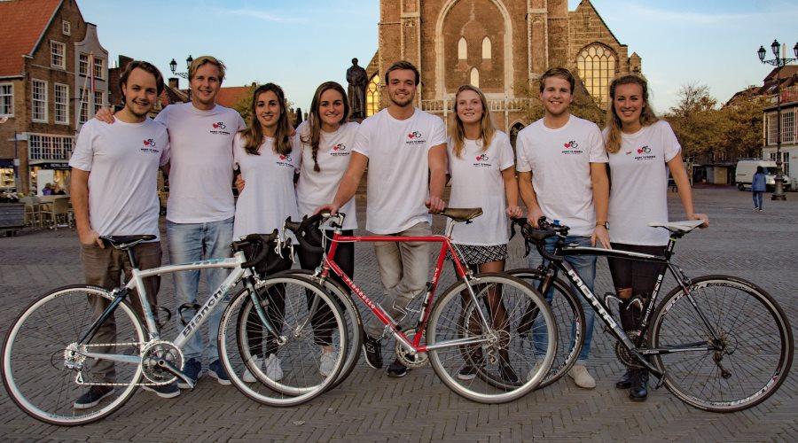 foto met 8 studenten van Universiteit Delft en hun fietsen